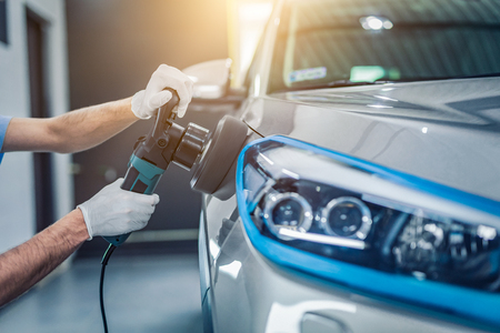 Foto per Car detailing - Man holds a polisher in the hand and polishes the car. Selective focus. - Immagine Royalty Free