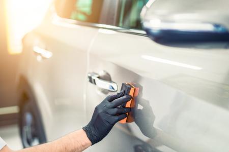 Photo pour Car detailing - Man applies nano protective coating to the car. Selective focus. - image libre de droit