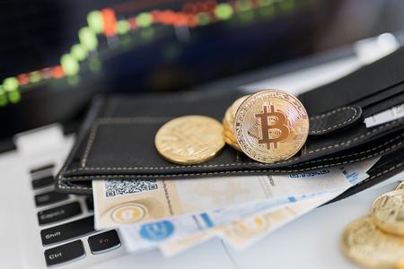Foto de Bitcoin gold coin and printed encrypted money with QR code - Imagen libre de derechos