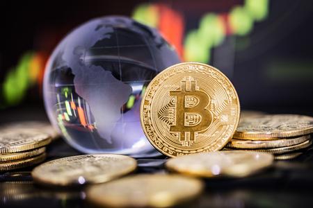Foto de Bitcoin gold coin and defocused chart background. - Imagen libre de derechos