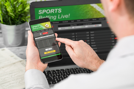 Foto de betting bet sport phone gamble laptop over shoulder soccer live home website concept - stock image - Imagen libre de derechos