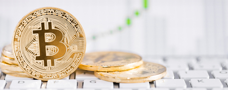 Foto de Bitcoin gold coin and defocused chart background. Virtual cryptocurrency concept. - Imagen libre de derechos