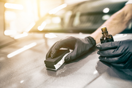 Foto per Car detailing - Man applies nano protective coating to the car. Selective focus. - Immagine Royalty Free