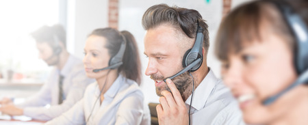 Foto de Call center worker accompanied by his team. Smiling customer support operator at work. Young employee working with a headset. - Imagen libre de derechos