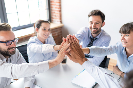 Foto de Business people happy showing team work and giving five in office. Teamwork concepts. - Imagen libre de derechos