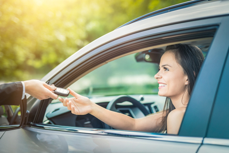 Photo pour A young beautiful woman receive the keys to the new car from the dealer. - image libre de droit