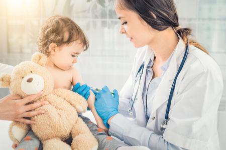 Foto de Young woman pediatrician performs a vaccination of a little girl. The girl is holding a mascot. - Imagen libre de derechos