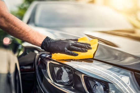 Foto de Car detailing - the man holds the microfiber in hand and polishes the car. Selective focus. - Imagen libre de derechos