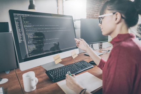 Foto de Developing programming and coding technologies. Website design. Programmer working in a software develop company office. - Imagen libre de derechos