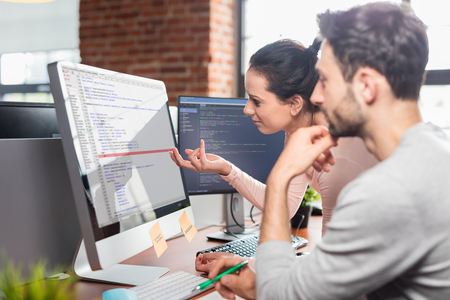 Foto de Developing programming and coding technologies. Website design. Programmer working in a software develop company office. - Imagen libre de derechos