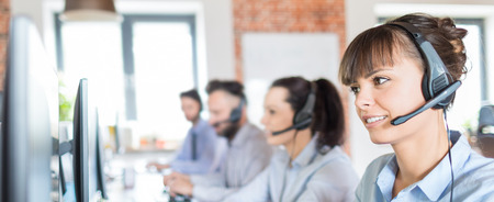 Photo pour Call center worker accompanied by her team. Smiling customer support operator at work. Young employee working with a headset. - image libre de droit