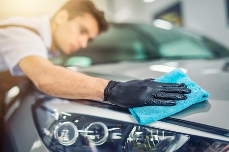 Photo for the man holds the microfiber in hand and polishes the car. Selective focus. - Royalty Free Image