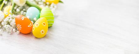 Foto de Easter eggs in a bird's nest on a wooden table. Flowers symbol of spring. - Imagen libre de derechos