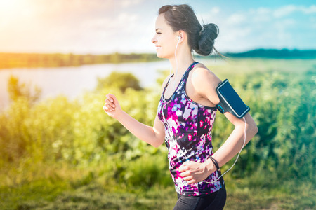 Photo pour Beautiful, young woman running on the water's edge by the country road. Jogging concept. - image libre de droit