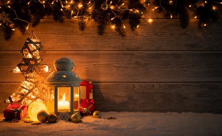 Photo for Christmas Card: snowy lantern and candlelight with fir branches and baubles on wooden background. - Royalty Free Image