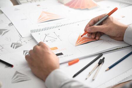 Foto de Graphic designer drawing sketches logo design. The concept of a new brand. Professional creative occupation with idea. - Imagen libre de derechos