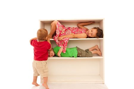 Three young kids playing on bookshelves, two lying on the shelves, with the youngest trying to get on.