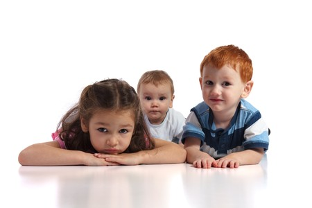 Three kids lying on floor facing camera. Isolated white background, foreground reflection.
