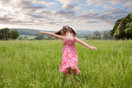 Photo pour Girl running through long grass field with arms outstretched - image libre de droit