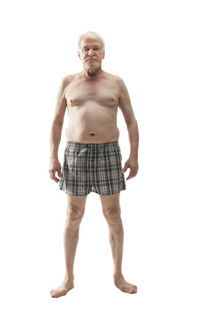 Foto per Elderly man posing in the studio in the nude cut out on a white background - Immagine Royalty Free