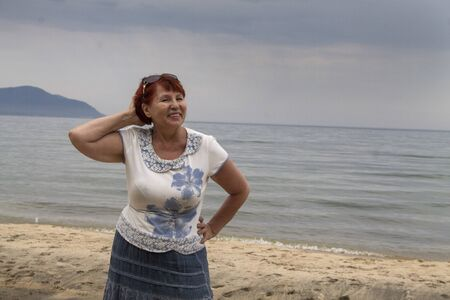 Photo for Beautiful elderly woman resting on the shore of Lake Baikal, enjoying the fresh sea air - Royalty Free Image