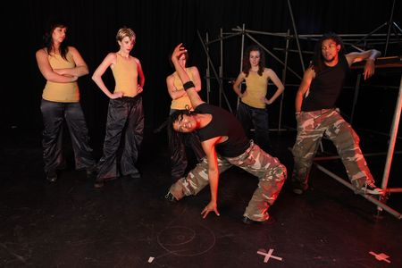 A group of female and one male freestyle hip-hop dancers during dance training session on stage. Lit with spotlights