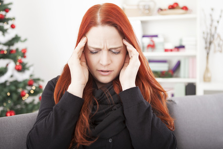 Foto de young red haired woman is sick and have headache on christmas - Imagen libre de derechos
