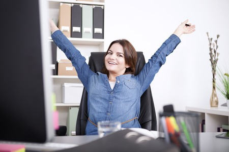 Photo pour Happy Female Executive Sitting on her Chair at the Office While Stretching her Arms and Looking at the Camera. - image libre de droit