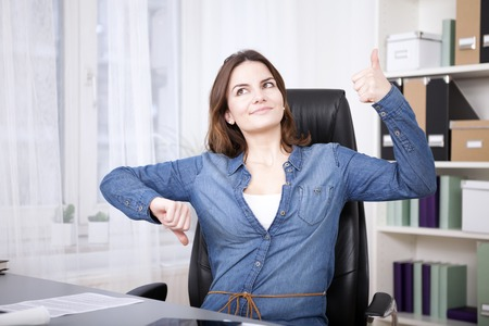 Foto de Close up Thoughtful Young Office Woman Sitting on her Chair Showing Thumbs Up and Down Hand Signs While Looking Up. - Imagen libre de derechos