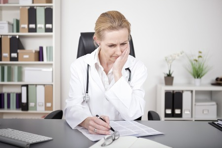 Photo pour Thoughtful Adult Female Doctor Studying Medical Findings on a Paper While Sitting at her Table - image libre de droit