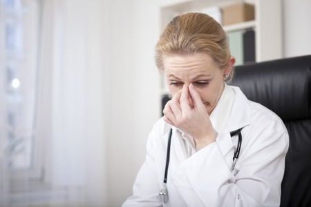Foto de Close up Stressed Adult Female Doctor Sitting at her Office and Holding her Nose Bridge While Looking Down - Imagen libre de derechos