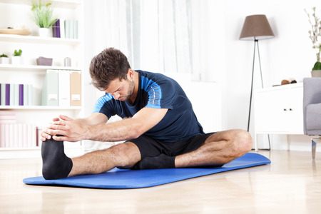 Photo pour Handsome Young Man Doing Hamstring Stretch Exercise on Top of a Mat at Home. - image libre de droit