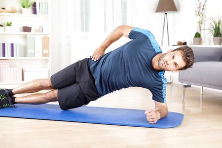Foto de Healthy Gorgeous Man Doing an Indoor Side Plank Exercise on a Mat While Looking at the Camera. - Imagen libre de derechos
