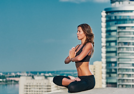 Photo for Yoga and meditation in a modern urbanistic city. Young attractive girl - yoga meditates against modern skyscrapers - Royalty Free Image