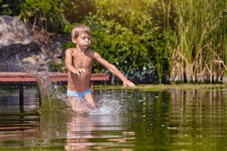 Foto de cute Boy jumping fun into the river - Imagen libre de derechos