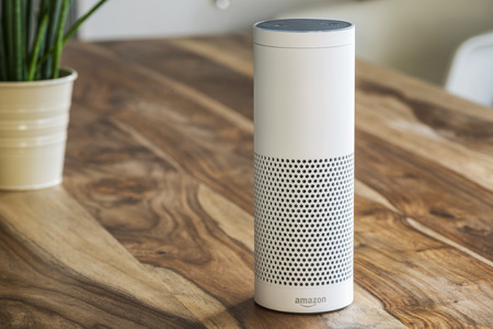Photo for MUENSTER - JANUARY 27, 2018: White Amazon Echo Plus, Alexa Voice Service activated recognition system photographed on wooden table in living room, Packshot showing Amazon Logo - Royalty Free Image