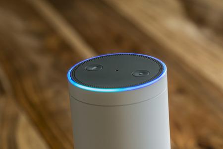 Foto de MUENSTER - JANUARY 27, 2018: White Amazon Echo Plus, Alexa Voice Service activated recognition system photographed on wooden table in living room - Imagen libre de derechos