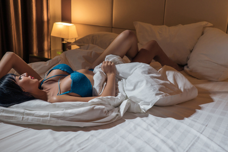 Photo pour Brunette with a beautiful figure and a big breast in revealing lingerie resting in bed - image libre de droit