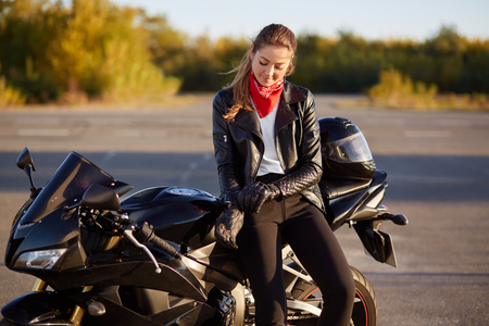 Foto de Outdoor shot of pleased female bikes puts on leather gloves, dressed in black clothes, poses on motorbike - Imagen libre de derechos