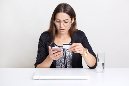 Foto de Puzzled young female blogger checks account, verifies number of plastic card, makes money transaction, uses wireless internet, has surprised expression in screen of smart phone - Imagen libre de derechos