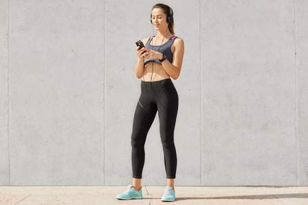 Foto de Sporty woman listening music in headphones while training in gymnasium, dressed top and legging, shows bared stomach, posing over gray studio background. - Imagen libre de derechos