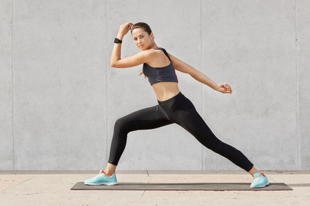 Photo pour Fit and healthy woman stretches before running, Caucasian female wearing tank top, black legging and blue sneakers doing sport exercises on mat in gym, model posing alone over grey background. - image libre de droit