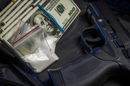 Photo pour Drug in the form of white powder in plastic bags on packs of dollars with a gun - image libre de droit