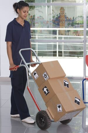 Side view of delivery woman in uniform pushing stack of cardboard boxes on dolly