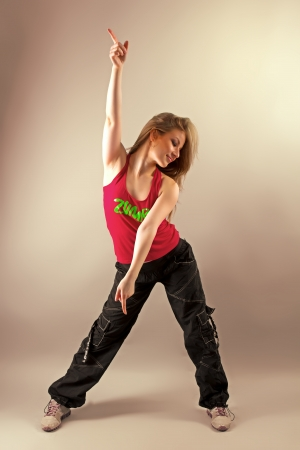 Photo for Young woman enjoying aerobics zumba fitness and raising her hand - Royalty Free Image