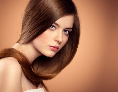 Beauty salon model with perfect long glossy brown hair posing in studio. Close-up portrait of lovely teenage girl with beautiful hairstyle.