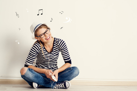 Photo for Portrait of happy female listening musical composition in earphones with sheet music and clef drawn on the wall. Young pretty Caucasian woman sitting on wooden floor in her house. - Royalty Free Image