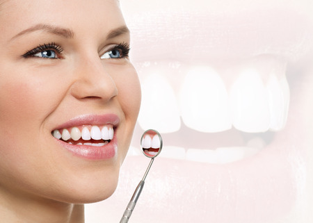 Photo pour Fresh smile. Teeth whitening. Oral check up. Portrait of young cheerful woman examining her teeth with dental mirror. - image libre de droit