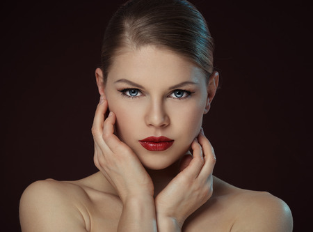 Lovely young female touching her clean face over black background. Close-up portrait of Caucasian fashion model with professional makeup and hairstyle posing in studio.