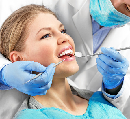 Dental health. Male dentist curing a female patient.